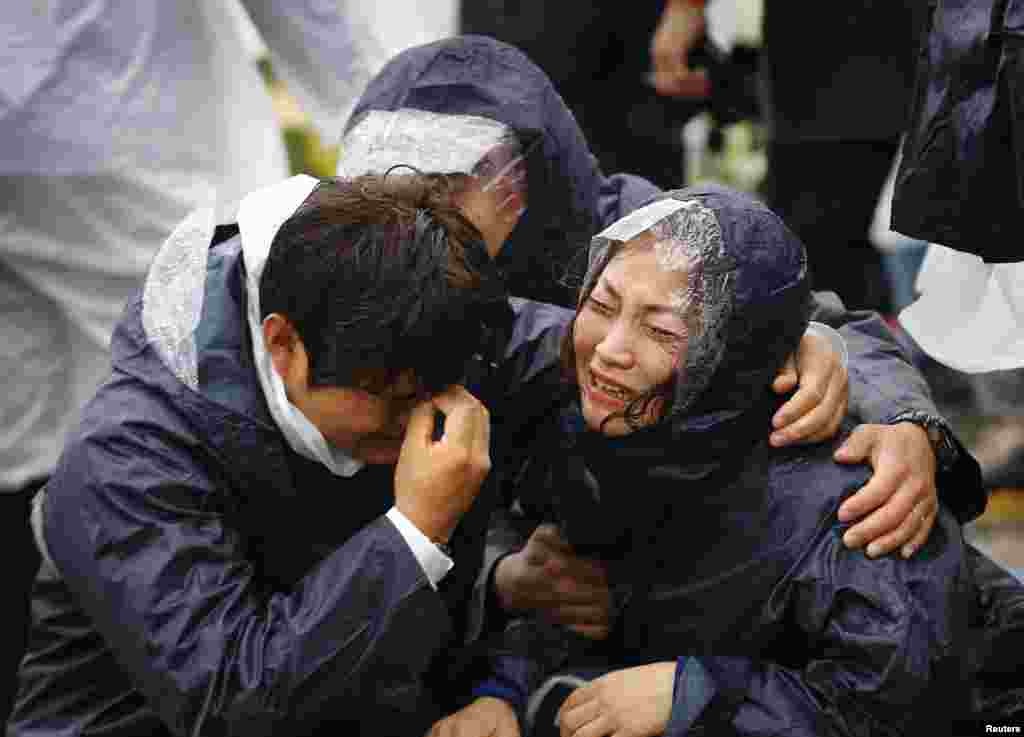 Family members of passengers missing on the overturned South Korean ferry Sewol react at the port in Jindo.
