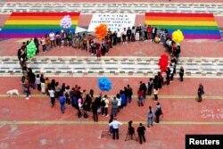 Anggota dan aktivis komunitas LGBTQ+ membentuk formasi berbentuk hati pada Hari Internasional Melawan Homofobia, Transfobia dan Biphobia di Mother Theresa Square, di tengah pandemi COVID-19 di Tirana, Albania, 17 Mei 2021. (REUTERS/Florion Goga)