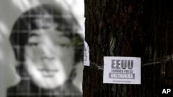 Foto de un desaparecido durante la última dictadura militar de Argentina detrás de un panfleto en un árbol que acusa a Estados Unidos de apoyar a ese régimen y protesta contra la visita del presidente Obama la próxima semana.