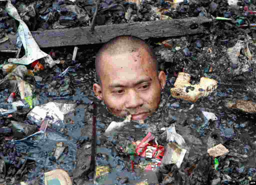 April 7: A man wades in neck-deep sea water filled with debris while searching for valuable items after a fire razed more than 500 houses along a village in Malabon city, north of Manila. The fire, believed to be caused by an exploding liquefied petroleu