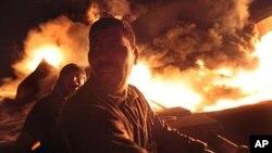 دوو پـیاو ههوڵی کوژاندنهوهی ئاگری ئهمبارێـکی سووتهمهنی له مسڕاته دهدهن که له لایهن هێزهکانی قهزافیـیهوه بۆردومان کراوه، شهممه 7 ی پـێـنجی 2011