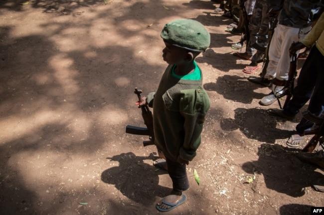 Serdadu anak yang baru dibebaskan bersiaga dengan senjatanya dalam upacara pembebasan di Yambio, Sudan Selatan, 7 Desember 2018.
