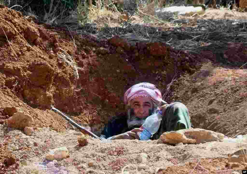 This citizen journalism image provided by ENN shows a Syrian rebel in a trench, in Idlib province, northern Syria, June 12, 2013.