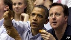 Οι κύριοι Ομπάμα και Κάμερον παρακολουθούν τον αγώνα μπάσκετ