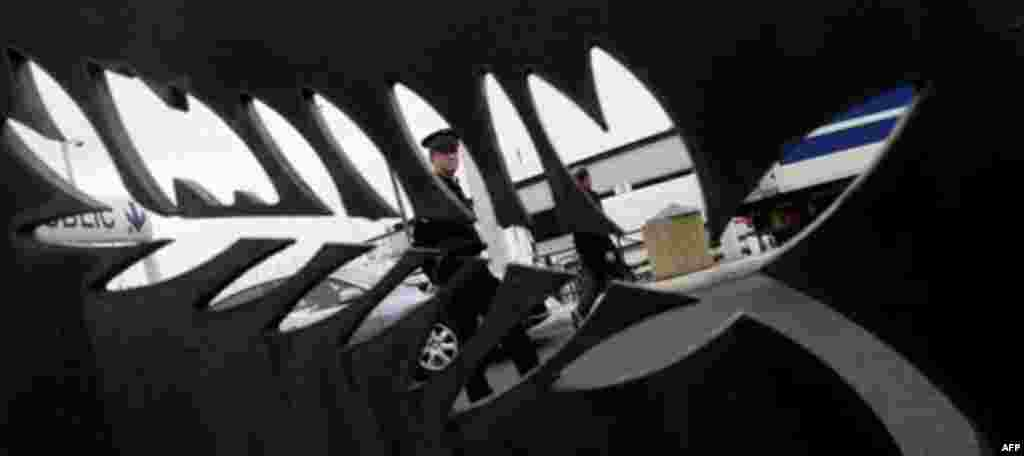 A police officer stands guard, behind the logo of Cannes, outside the media center of the G20 in Cannes, France on Wednesday, Nov. 2, 2011. French President Nicolas Sarkozy will hold emergency talks Wednesday with European leaders in a last-ditch bid to s