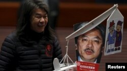 Lawmaker Leung Kwok-hung, demanding better welfare for the elderly, carries a mocking portrait of Hong Kong Financial Secretary John Tsang before Tsang's annual budget report at the Legislative Council in Hong Kong, Feb. 24, 2016.