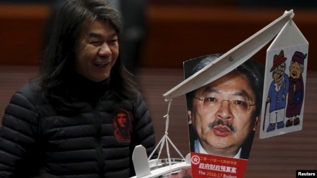 Lawmaker Leung Kwok-hung, demanding better welfare for the elderly, carries a mocking portrait of Hong Kong Financial Secretary John Tsang before Tsang's annual budget report at the Legislative Council in Hong Kong, Feb. 24, 2016.