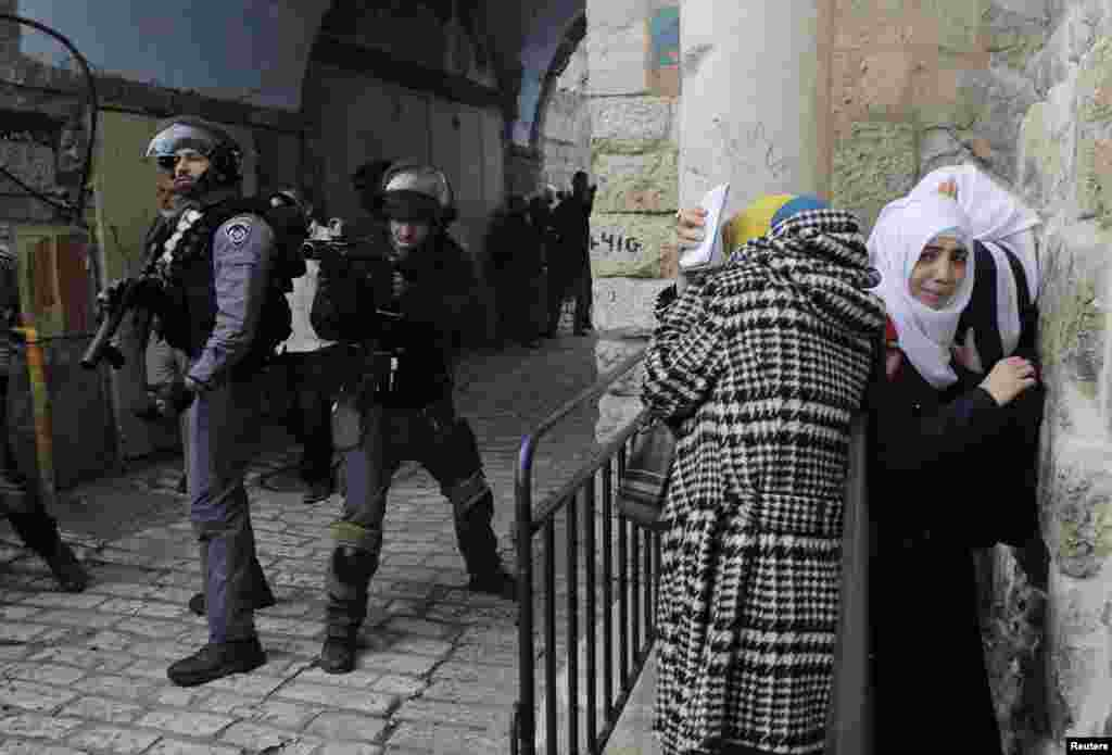 Palestinian women take cover as Israeli police use stun grenades to disperse a crowd trying to enter the compound known to Muslims as the Noble Sanctuary and to Jews as the Temple Mount in Jerusalem's Old City, Nov. 5, 2014.