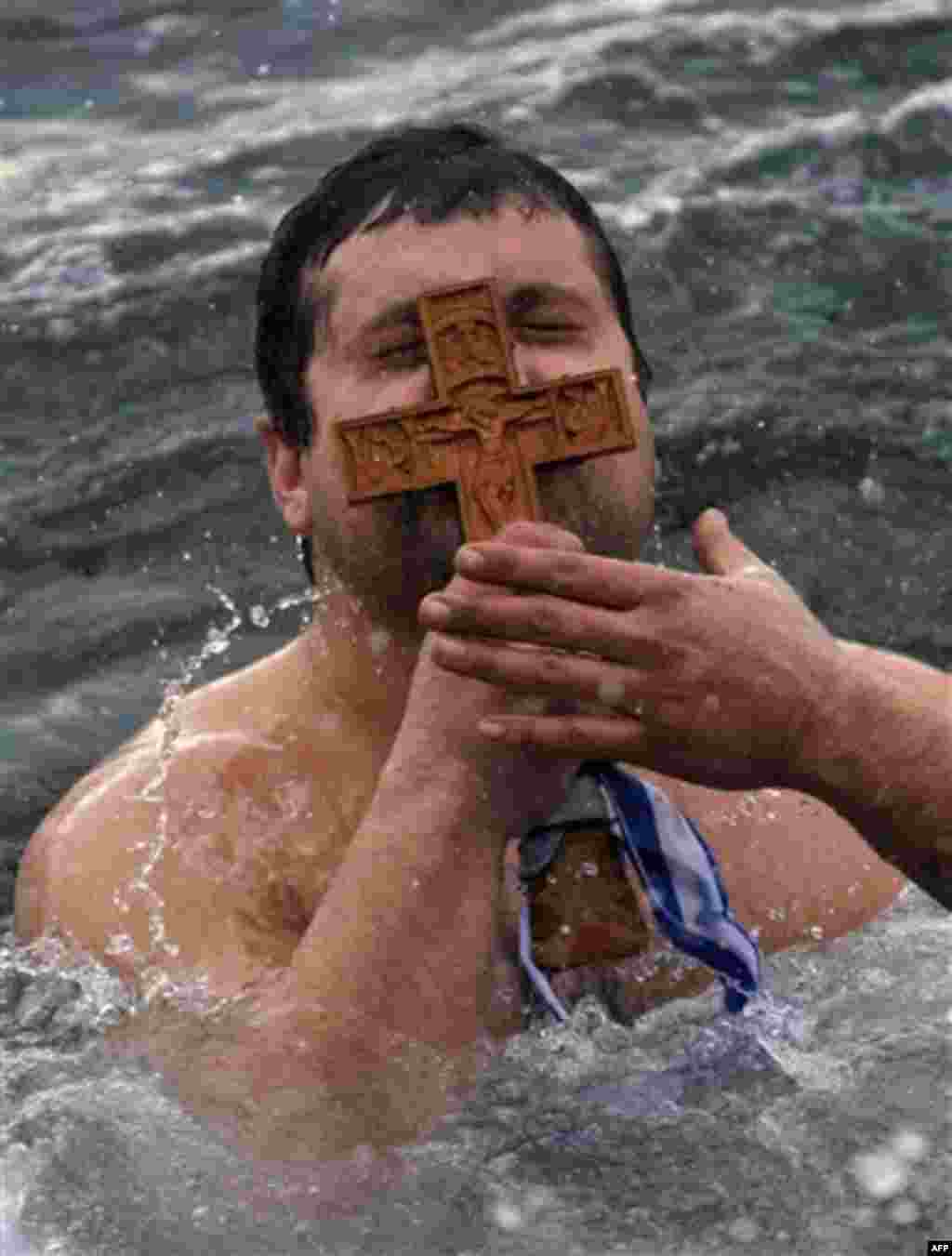Panagiotis Mantziaris, kisses the wooden cross after being the first to retrieve it, during an Epiphany ceremony to bless the water in Greece's northern port city of Thessaloniki, Friday, Jan. 6, 2012. Similar ceremonies to mark Epiphany day were held acr