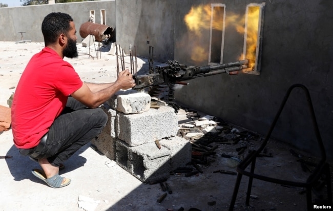 A fighter loyal to Libyan internationally recognized government fires a heavy machine gun during clashes with forces loyal to Khalifa Haftar at outskirts of Tripoli, Libya, May 16, 2019.