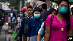 FILE - People wearing masks to protect themselves against the swine flu virus, July 27, 2017, in Yangon, Myanmar.