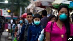 People wearing masks to protect themselves against the swine flu virus in Yangon, Myanmar, July 2017. (AP Photo/Thein Zaw)