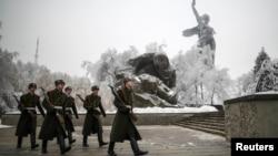 """Para anggota Pasukan Kehormatan Rusia berjalan di sekitar patung """"Motherland Calls"""" di Volgograd, Rusia (31/12)."""
