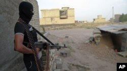 FILE - A masked anti-government gunman holds his weapon as he stands guard in Fallujah, Iraq.