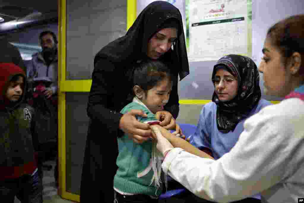 A Syrian girl cries after receiving the measles vaccine from UNICEF nurses at the U.N. refugee agency's registration center in Zahleh, Lebanon, Dec. 18, 2013.