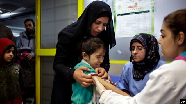 A Syrian girl cries after receiving the measles vaccine from UNICEF nurses Nadine Houjairi (2nd R), and Genivieve Bashalani (R) at the U.N. refugee agency's registration center in Zahleh, in Lebanon's Bekaa Valley, Dec. 18, 2013.