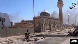 File - An image grab taken from a video allegedly shows Islamic State fighters in a street of Ramadi, Iraq.