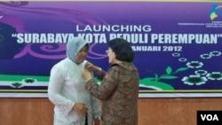 """Staf Ahli Menteri Pemberdayaan Perempuan dan Perlindungan Anak, Emmy Rachmawati memasangkan PIN """"Surabaya Kota Peduli Perempuan"""" kepada Walikota Surabaya Tri Rismaharini (19/1)."""
