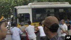 越南警察7月10日将一名在中国驻河内大使馆前抗议的示威者拖向一辆汽车