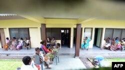 Des femmes, certaines avec leurs bébés, sont assises dans les couloirs de la maternité de Binza, à Kinshasa, le 7 mai 2013.