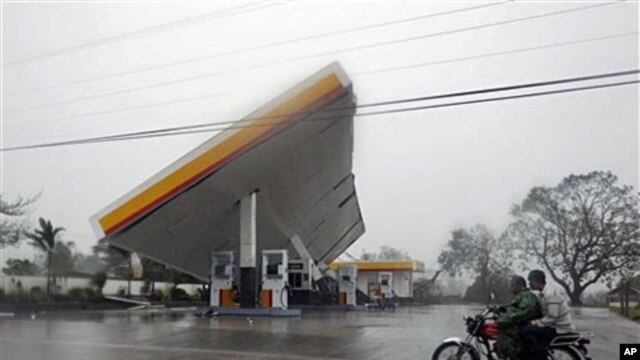 "Motorists drive past a filling station which was toppled by typhoon Megi (local name ""Juan""), 18 Oct 2010, at Cauayan, Isabela province, northeastern Philippines"