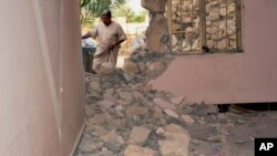 FILE - A man inspects his house damaged after a bomb attack by Islamic State group extremists in Khalidiya, 60 miles (100 kilometers) west of Baghdad, Sept. 20, 2015.