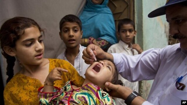 A Pakistani health worker gives a polio vaccine to a child in Rawalpindi, Pakistan, Tuesday, May 6, 2014. Pakistan's health minister says the country is taking extra ordinary measures to meet the new situation it is going to face after polio travel restri