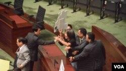 社民連立法會議員梁國雄高舉示威標語,被多名立法會保安員帶離會議廳。 (美國之音 湯惠芸攝)