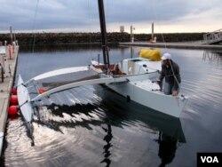Joe Bersch prepping the Team Pure & Wild proa, a type of multihull sailing vessel, before the sail to Ketchikan, Alaska. (Tom Banse/VOA)