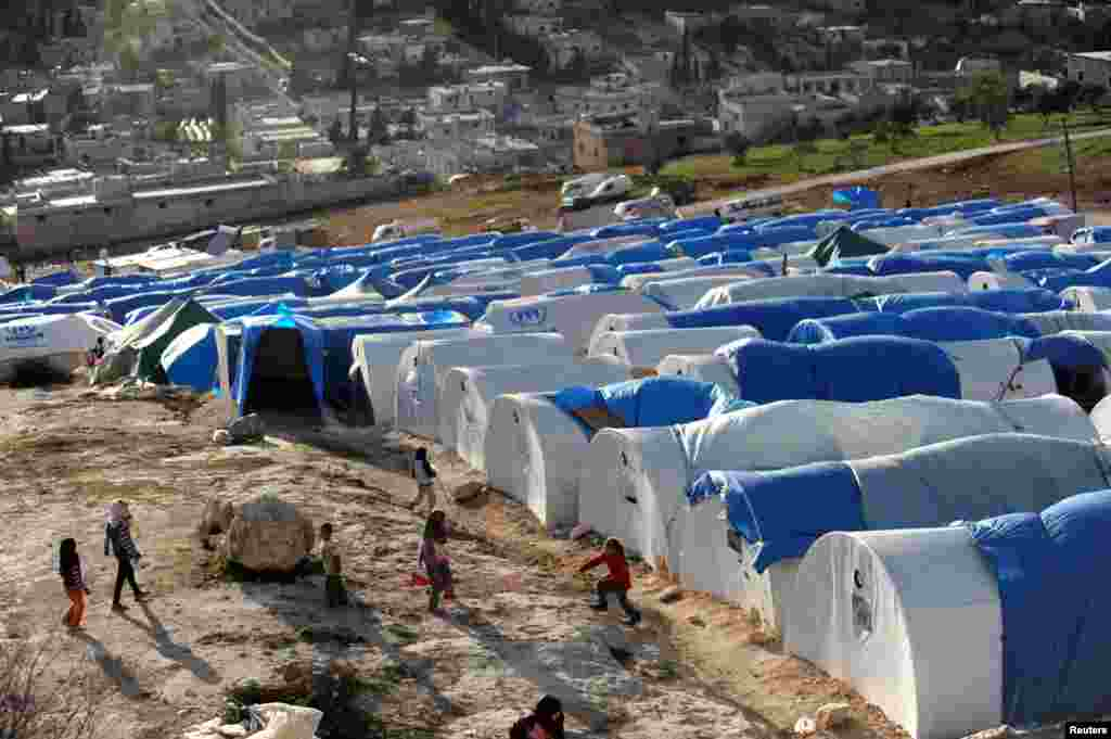Anak-anak di Suriah bermain di luar tempat tinggal darurat mereka di kamp pengungsi Qah, desa Atme, provinsi Idlib (17/3).