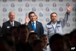 Guatemala's President Jimmy Morales, center, stands between Guatemala City Mayor Alvaro Arzu, left, and Villa Nueva Mayor Edwin Escobar during a meeting with city mayors in Guatemala City, Aug. 29, 2017.