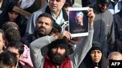 Čovek drži sliku ubijenog Kasema Sulejmanija tokom današnjih demonstracija u Teheranu (Foto: AFP/Atta Kenare)