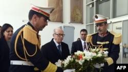 突尼斯总统埃塞朴西(中)在国家博物馆入口处放置花圈,悼念袭击事件遇害者