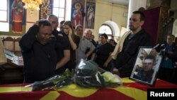 Relatives of slain policeman Sasho Samoilovski mourn next to his coffin covered in Macedonian flag inside a church in the town of Tetovo, Macedonia, May 10, 2015.
