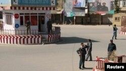 شہر میں دکانیں بند ہیں اور افغان پولیس اہلکار اپنی ایک چوکی کے پاس کھڑے ہیں