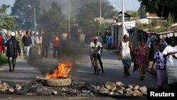 布隆迪总统决定竞选第三任期引发民众抗议,人们走过首都布琼布拉街头燃烧的路障(2015年5月13日)