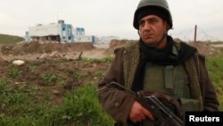 A Kurdish peshmerga fighter keeps watch in Zumar, Nineveh province, near Mount Sinjar, Dec. 18, 2014.