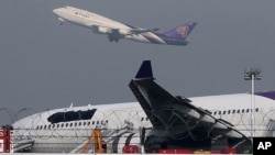 FILE - A Thai Airways passenger plane takes off over a damaged Thai Airways Airbus A330-300 that skidded off the runway while landing at Suvarnabhumi International Airport in Bangkok, Thailand, Sept. 9, 2013.