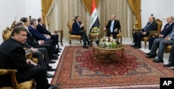 Iraq's President Barham Salih, right, meets with U.S. Energy Secretary Rick Perry, in Baghdad, Dec. 11, 2018.
