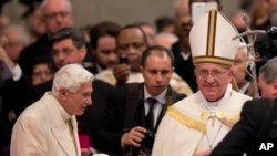 Paus Fransiskus (kanan) menyalami Paus Emeritus Benediktus XVI seusai upacara pelantikan kardinal baru di Basilika Santo Peter, Vatikan (22/2).