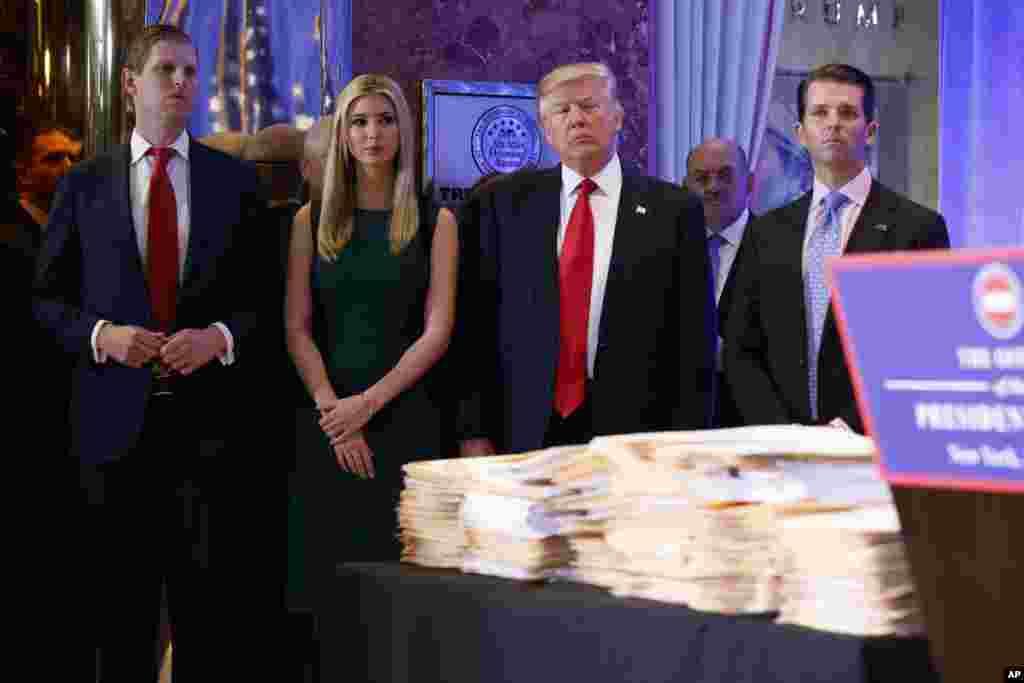 Presiden AS-terpilih, Donald Trump, didampingi oleh keluarganya, tiba di konferensi pers di lobby Trump Tower di New York.