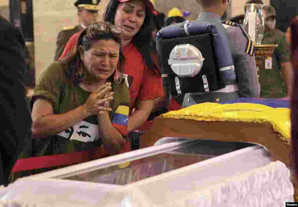 Supporters of late Venezuelan President Hugo Chavez react as they view his coffin during a wake at the military academy in Caracas, March 7, 2013.