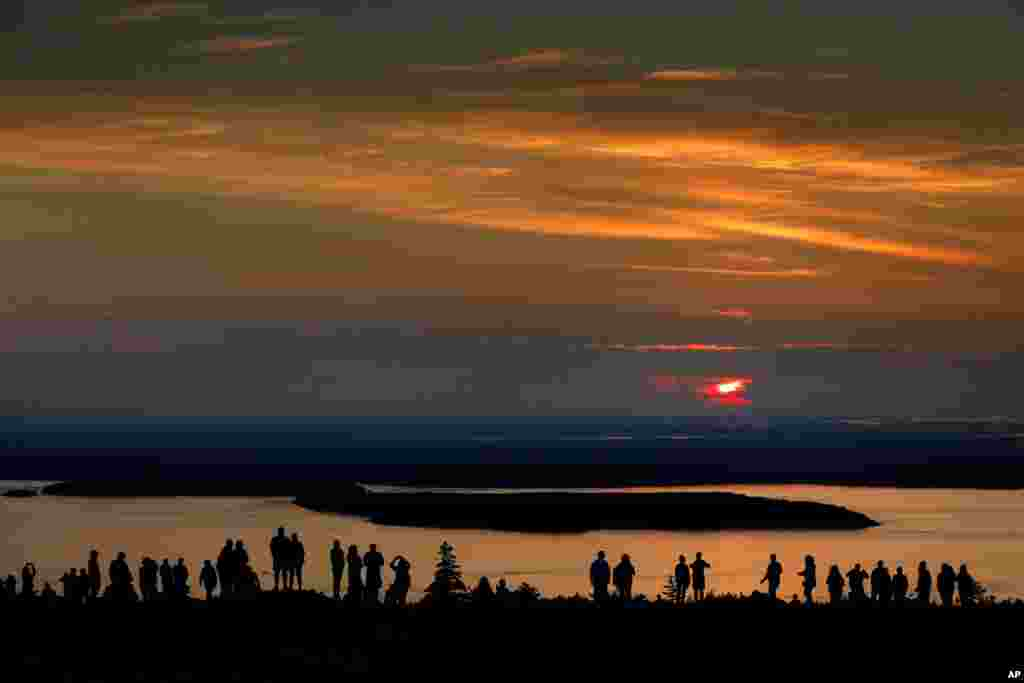 A crowd gathers near the summit of Cadillac Mountain in Acadia National Park to be among the first in the continental United States to see the sunrise, near Bar Harbor, Maine.