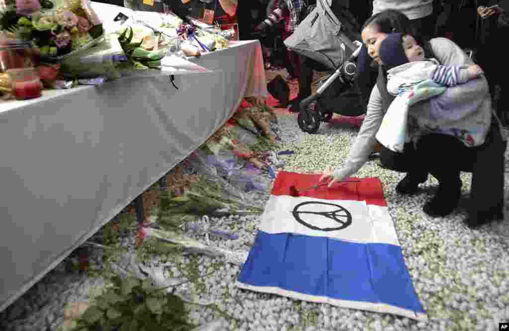 A woman offers a flower during a vigil for the victims of Friday's attacks in Paris, at the French Embassy in Tokyo, Nov. 15, 2015.