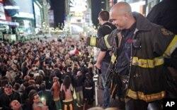 Un sapeur-pompier new yorkais saluant la foule célébrant la mort de Bin Laden à Time Square (New York)
