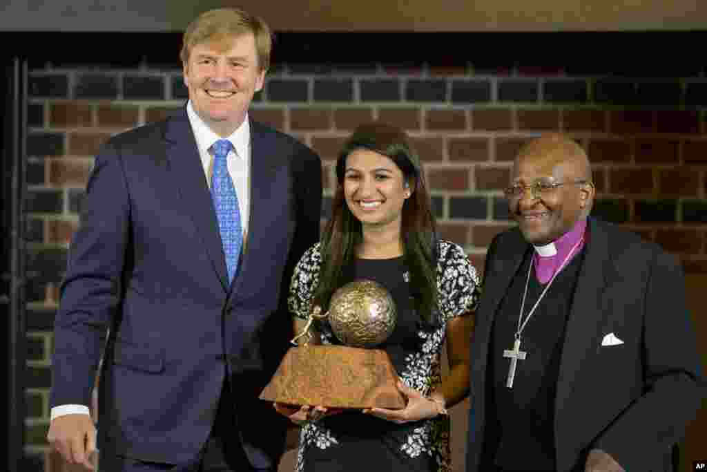 Eighteen-year-old American Neha Gupta poses with Dutch King Willem Alexander (l) after receiving the KidsRights Children's Peace Prize from South African Archbishop Emeritus Desmond Tutu (r) in The Hague, Netherlands.