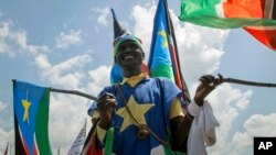 FILE - A man waves South Sudanese national flags during peace celebrations in the capital Juba, South Sudan, Oct. 31, 2018.