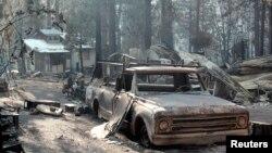 """Sebuah bangunan dan mobil yang terbakar akibat kebakaran """"Rim Fire"""" di dekat Taman Nasional California (27/8)."""