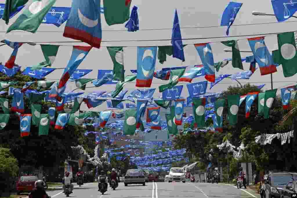 Motorists drive underneath flags of Malaysia's ruling party National Front, opposition Pan-Malaysian Islamic Party and People's Justice Party ahead of the upcoming general elections in Kuala Lumpur.