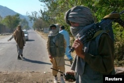 FILE - Masked Pakistani pro-Taliban militants stand at a check post in Charbagh, a Taliban stronghold, near Mingora, the main town of Pakistan's Swat Valley, Nov. 2, 2007.